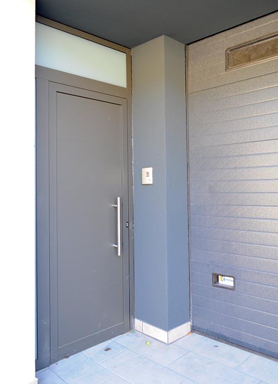 Porta d'entrada d'alumini RAL 7022 texturat amb panell cec
